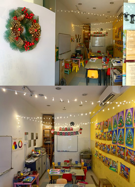 Christmas celebration / party at our art studio, there is a Christmas wreath at the door, Christmas lights hang on the ceiling and a Christmas banner on the wall