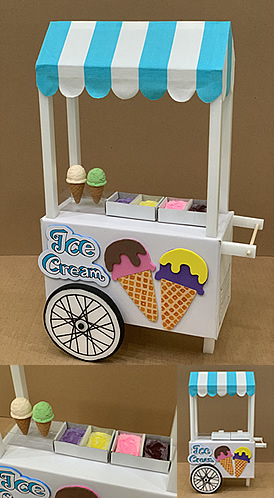 Picture 1: a wheeled ice cream cart with a blue and white stripy fabric as canopy. On the cart, clay cone ice creams on a display stand and different flavours of clay ice cream in the freezer compartments. At the side, a logo and foam sheep cone ice creams as design. Picture 2: enlarged photo of the clay ice creams. Picture 2: freezers covers are placed on freezer compartments and cone ice cream removed to show that they are removable.