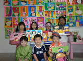 Kids with their pie paintings infront of a wall of children artwork