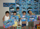 Kids with their shark paintings infront of a wall of children artwork