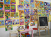 A wall full of children paintings and artwork